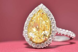Two Tone 18 Karat Halo Ring With One 3.51Ct Pear Fancy Light Yellow VS2, GIA Certified Diamond And 38=0.64Tw Round F VS1 Diamonds